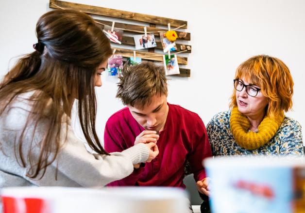 Zwei Mitarbeiterinnen unterstützen einen Klienten beim Essen. Eine Mitarbeiterin reicht einem jungen Mann mit Behinderung Essen.