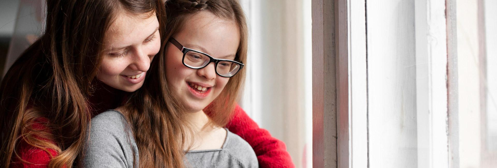 Eine ehrenamtliche Mitarbeiterin unterstützt eine junge Frau mit Behinderung.
