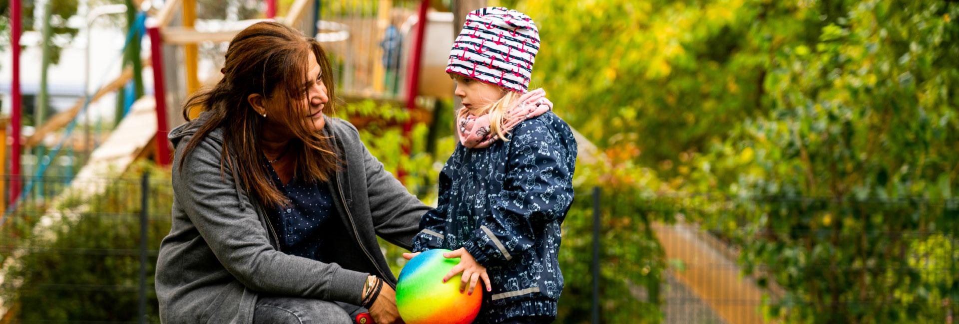 Eine Pädagogin betreut ein Mädchen in der Kita Kinderland. Die beiden spielen gemeinsam Ball.