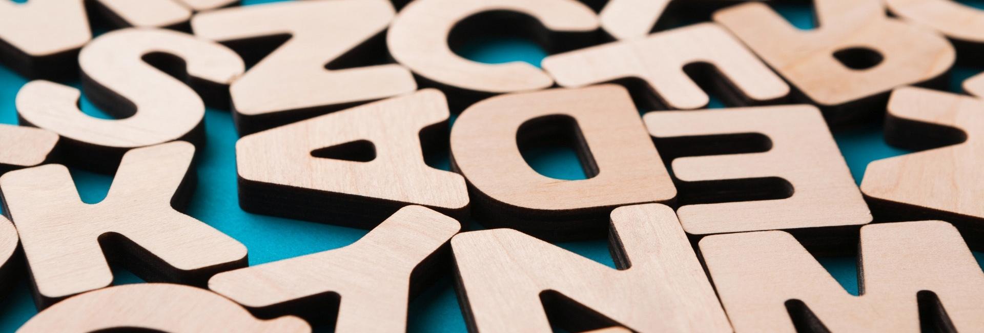 Große abgerundete Holzbuchstaben liegen auf einem blauen Tisch.