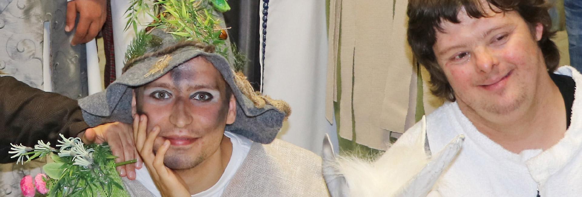 """Zwei Schauspieler:innen mit Behinderung sind geschminkt und verkleidet. Eine Schauspielerin ist als Waldgeist verkleidet. Der andere Schauspieler ist als Einhorn verkleidet und hat eine Behinderung. Sie führen das Musical """"Das tapfere Schneiderlein"""" auf."""
