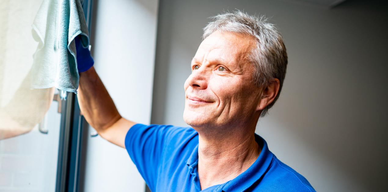 Ein Mitarbeiter reinigt ein Fenster. Er trägt ein blaues Lebenshilfe T-Shirt. Der Mann lächelt.
