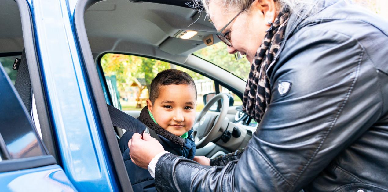Eine Mitarbeiterin des Fahrdienstes schnallt einen Jungen im Auto der Lebenshilfe an. Der Junge lächelt.