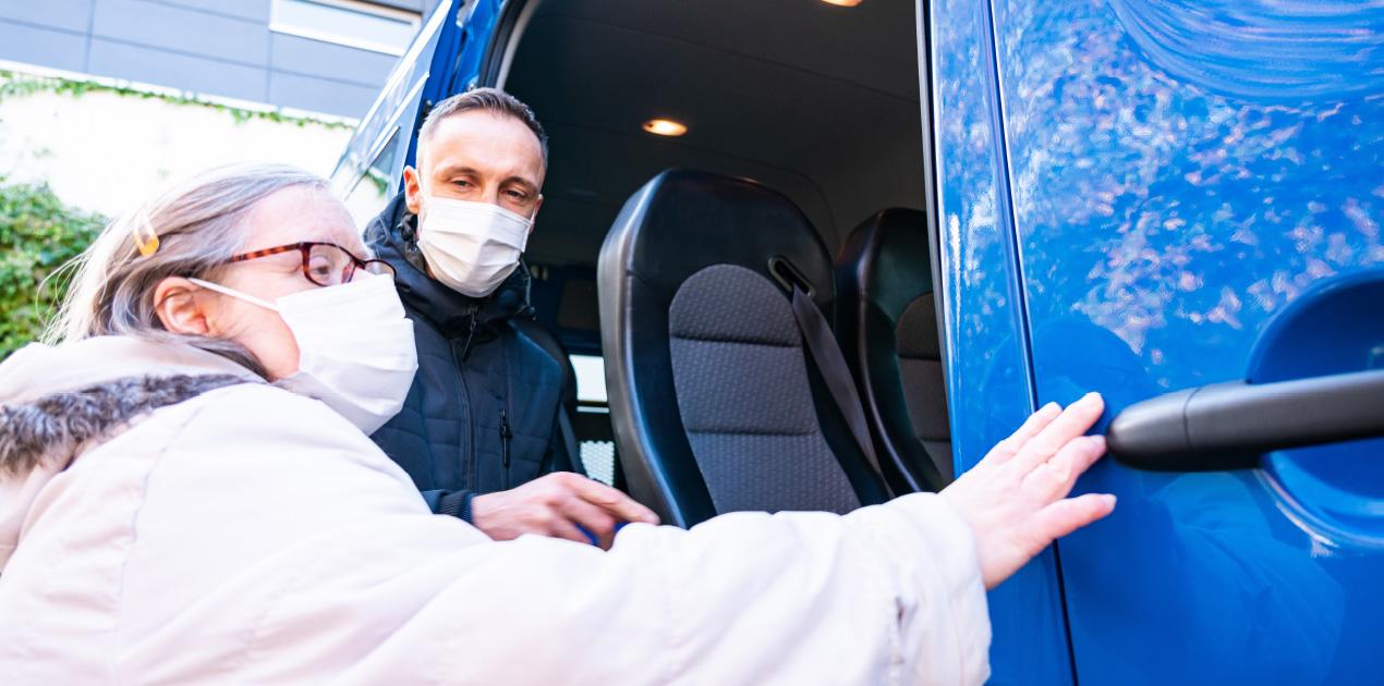Ein Mitarbeiter des Fahrdienstes hilft einer Klientin beim Einsteigen in das Lebenshilfe-Auto. Das Auto ist blau und die Tür ist weit geöffnet. Beide tragen eine Maske.