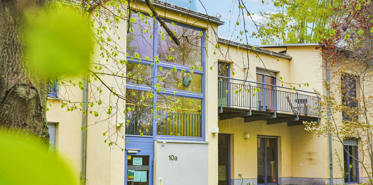 Die Wohnstätte 10a ist ein großes modernes Wohngebäude. Das Haus hat eine gelbe Fassade, zwei große Erker und in blau abgesetzte Fensterrahmen. Die Fenster sind bodentief.