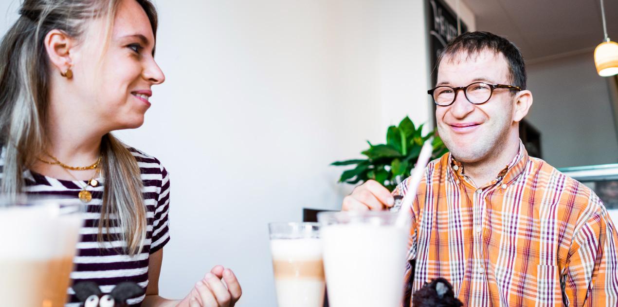 Eine Frau und ein Mann sitzen an einem Tisch und trinken gemeinsam einen Kaffee im MIA Café der Lebenshilfe Erfurt. Sie reden mit einander. Die Stimmung ist ausgelassen.