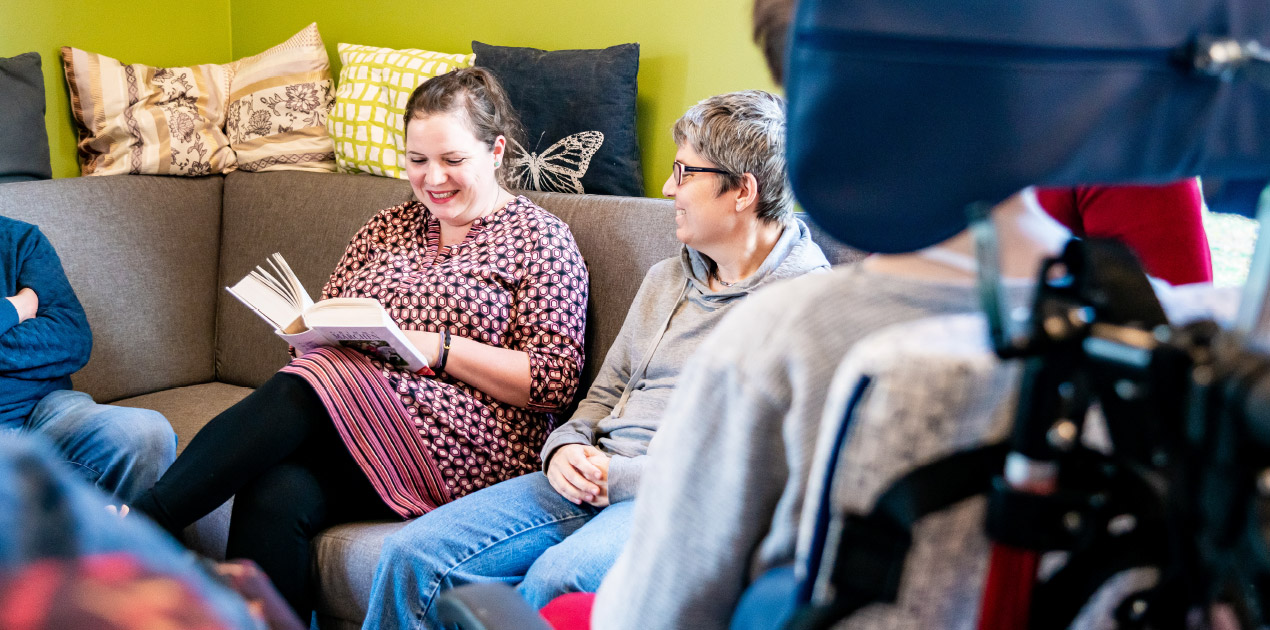 Eine Mitarbeiterin der Lebenshilfe Erfurt liest zwei Klient:innen aus einem Buch vor. Eine ältere Frau lächelt. Die Gruppe sitzt auf einem grauen Sofa im Gemeinschaftsraum.