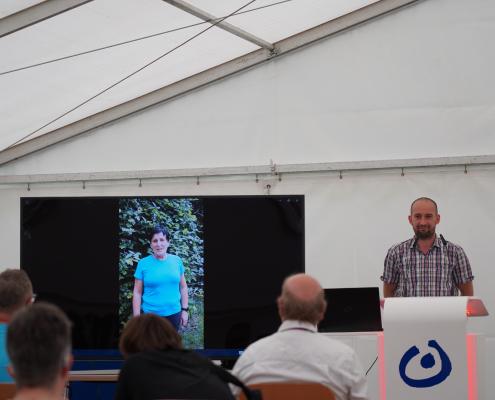 Ein Person steht am Rednerpult. Daneben läuft ein Video auf einem Bildschirm.