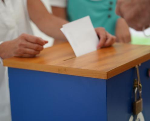 Ein Zettel wird in eine Wahlurne gesteckt.