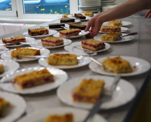 Kuchenstücke stehen auf Tellern bereit.
