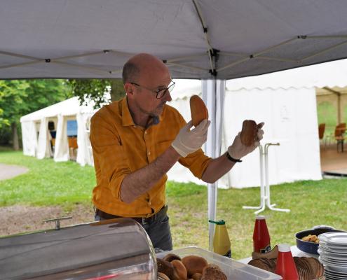 Herr Lehmann hält fragend zwei Brötchen am Grill in die Luft.
