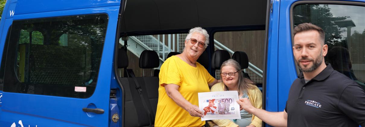 Frau Scheper und eine Bewohnerin sitzen in einem Bus der Lebenshilfe Erfurt. Herr Schramm überreicht die Spende an die beiden.